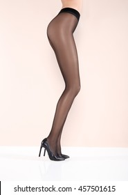 Beautiful legs of young woman in tights and black shoes