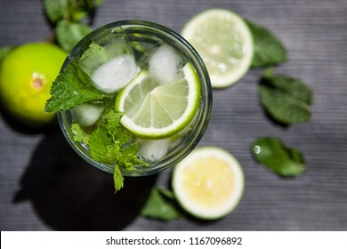 Beautiful Lemonade or Mojito coctail with lime, mint and ice, fresh drink on black table