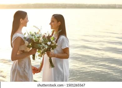 Beautiful lesbian couple on their wedding day near river