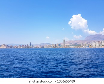 Beautiful Levante beach in Benidorm, Spain. Image taken from the sea, with the skyline of skyscrapers and a boat of first motive. Concept of holidays in Benidorm.