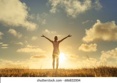 It's a beautiful life. Happy people lifestyle. Young woman in a nature setting with her arms in the air feeling free and energized.