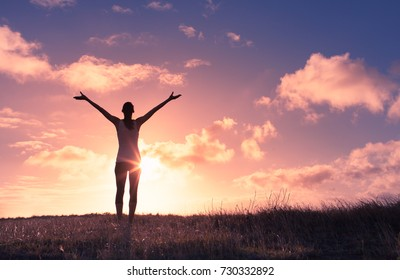 It's a beautiful life. Happy woman with arms up in the sunset.