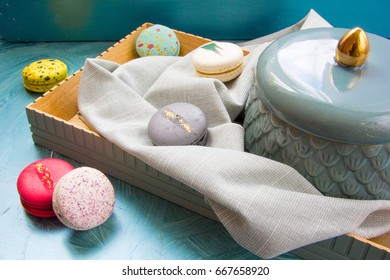 Beautiful lifestyle food picture in blue and grey colors: vintage wooden tray, ceramic vase with macarons and cotton serviette