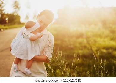 Beautiful lifestyle shot of young caucasian mommy spend happy time with her baby girl in summer over sun lights on sunset evening. Little toddler learns to explore the world of nature with his mother