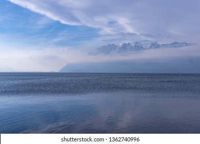 Beautiful light blue nature background of sky, mountains and sea. Still water surface.of the Leman (Geneva) lake and the Alps, view from Switzerland