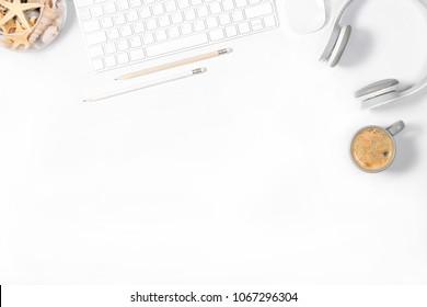 Beautiful light minimalistic mockup. White modern keyboard, mouse, headphones, pencils, vase with seashells and small cup of coffee on white background. Enjoying little things. Top view. Flat lay.