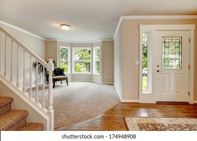 Beautiful light tones hallway with chair and palm open to entrance hall