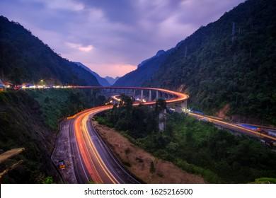 Beautiful light trail in the stretch of winding road of Kelok 9 in the evening, Payakumbuh / Pekan Baru Road, West Sumatra, Indonesia
