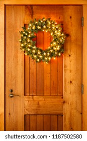 Beautiful lighted evergreen wreath with lights hanging on wooden front door of home background. Simple, rustic country style Christmas holiday home decorations.