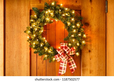 Beautiful lighted evergreen wreath with plaid fabric ribbon bow and lights hanging on wooden front door of home background. Simple, rustic country style Christmas holiday home decorations.