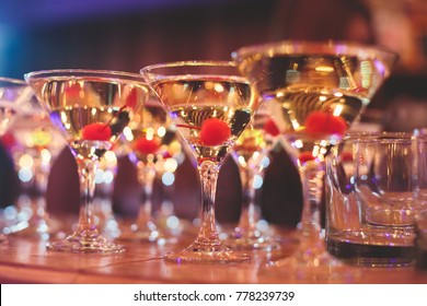 Beautiful line of different coloured cocktails on a Christmas party, tequila, martini, vodka, and others on decorated catering bouquet table