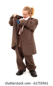 Beautiful little 7 year old girl in baggy suit looking for money in pocket over white background.