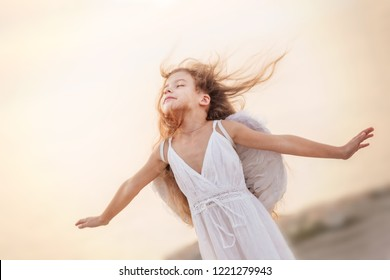 Beautiful little angel girl flying with closed her eyes, her hair is blowing in the wind