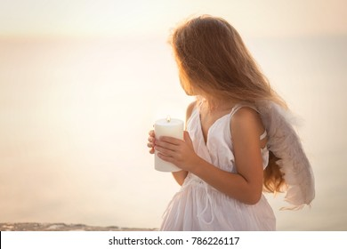Beautiful little angel girl holding a white candle and looking into the distance