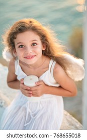 Beautiful little angel girl with perfect smile is holding a white candle.