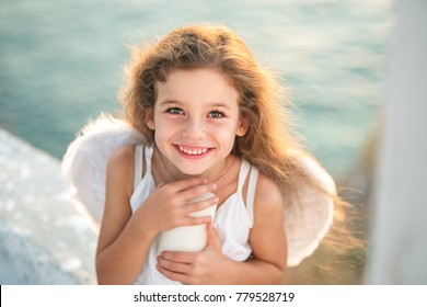 Beautiful little angel girl with perfect smile holding a white candle.