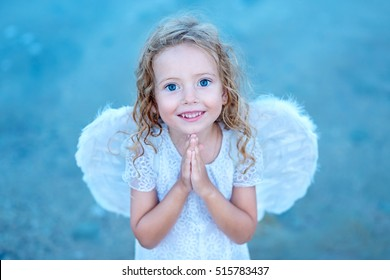 Beautiful little angel girl standing with your arms close to your chest as in prayer