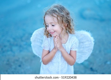 Beautiful little angel girl standing with your arms close to your chest as in prayer. Soft focus.