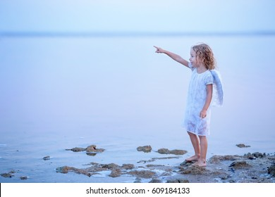 Beautiful little angel girl standing and pointing a finger at the sky