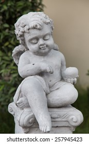 Beautiful little angel statue in garden ,hand focus