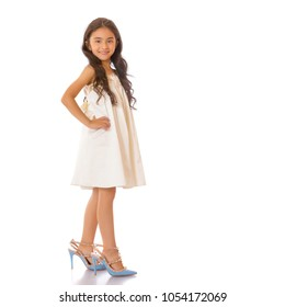 Beautiful little Asian girl with long black hair, in high-heeled shoes. Concept of style and fashion, happy childhood. Isolated on white background.