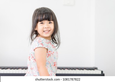 Beautiful little asian girl playing piano in living room or music school.Kindergarten child having fun with learning to play music instrument.Education, skills concept.