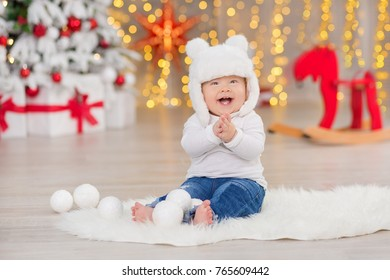 Beautiful little baby boy celebrates Christmas. New Year's holidays. Baby in a Christmas costume casual clothes with gifts on fur close to new year tree in studio decorations
