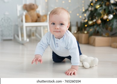 Beautiful little baby boy celebrating Christmas. Funny baby girl wearing santa claus hat and suit playing with Christmas ball over Christmas tree in room. Holiday season.