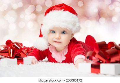 Beautiful little baby celebrates Christmas. New Year's holidays. Baby in a Christmas costume with gift