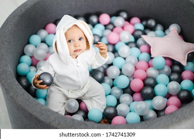 beautiful little baby gerl sitting in colorful balls in overalls with rabbit ears.