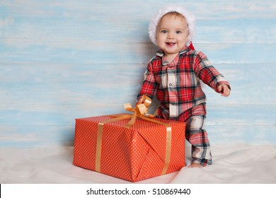 Beautiful little baby with gift celebrates Christmas. New Year's holidays. Baby with christmas background