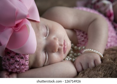 Beautiful little baby girl with bow and pearls sleeping peacefully on fur blanket