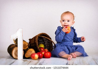 Beautiful little baby girl eating apple and celebrating her first birthday