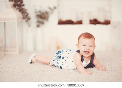 Beautiful little baby girl lies on a light carpet in the room
