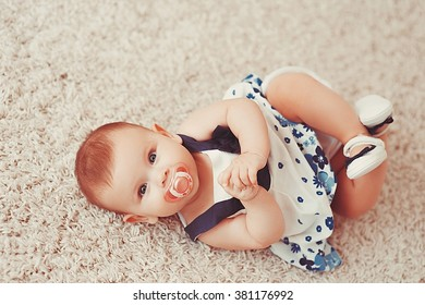 Beautiful little baby girl lies on a light carpet on his back with a pacifier in his mouth