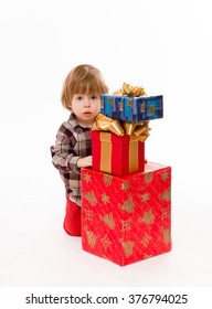 Beautiful little baby hiding behind presents over white background. Baby with serious glance waiting for Santa Clause.