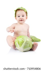 Beautiful little baby on a white background with green cabbage.