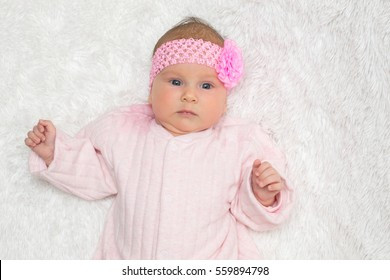 beautiful little baby with a pink bandage on a head lies on a white plaid