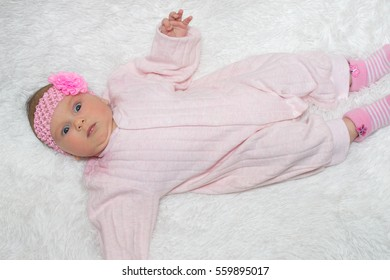 beautiful little baby with a pink bandage on a head lies on a white rug and stares