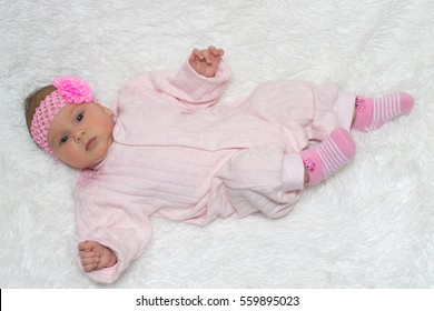 beautiful little baby with a pink bandage on a head lies on a white rug