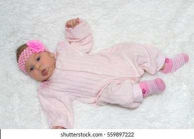 beautiful little baby with a pink bandage on a head lies on a white rug and showing tongue