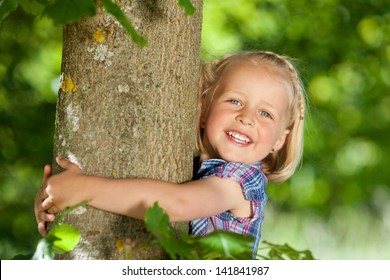 Beautiful little blond girl hugging a tree looking at the camera with a lovely happy smile