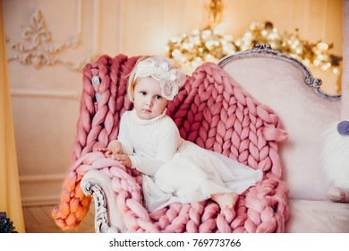beautiful little blond girl in white dress sits on a classic couch with a pink plaid in a nice light interior on the background of a fireplace decorated for Christmas lights