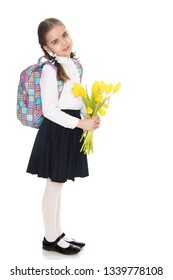 Beautiful little blond schoolgirl, with long neatly braided pigtails. In a white blouse and a long dark skirt.She is holding a bouquet of yellow tulips.Isolated on white background.