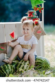Beautiful little blonde girl of about watermelon stalls. In a white tee shirt. With two curly tails. Summer. Joy. Keep a slice of watermelon on a stick!