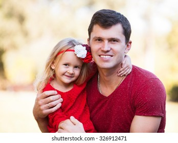 Beautiful little blonde girl and her father, has happy fun cheerful smiling face, red clothes. Family portrait nature.