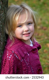 beautiful little blonde girl leaning against tree