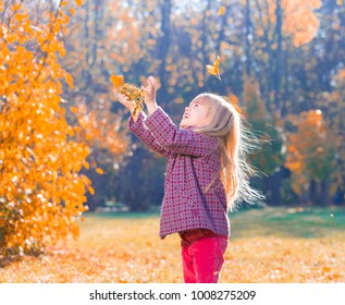 Beautiful little blonde hair girl, has fun smile face, happy emotions, dressed woolen coat. Plays falling leaves. Child portrait. Creative concept. Autumn time. Close up. Fashion kid style.