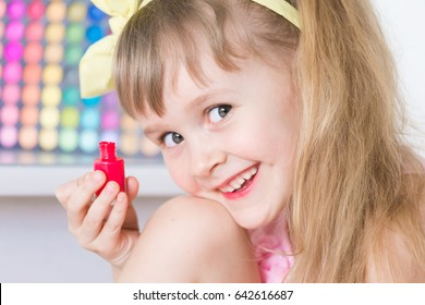 Beautiful little blonde hair girl, has happy smiling face, fun eyes, long hair, paints nails, make manicure,. Child portrait. Creative concept. Make up kids. Close up.