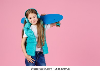 Beautiful little blonde kid girl 7-10 years old in jacket posing isolated on pastel pink background children portrait. Childhood lifestyle concept. Mock up copy space. Hold blue skateboard